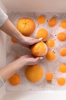 Mulher lavando laranja madura, toranja sob torneira na cozinha pia, embebendo frutas em água com sabão lava completamente após a loja