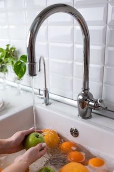 Mulher lavando maçã sob torneira na cozinha pia, embebendo frutas em água com sabão lava completamente após a loja