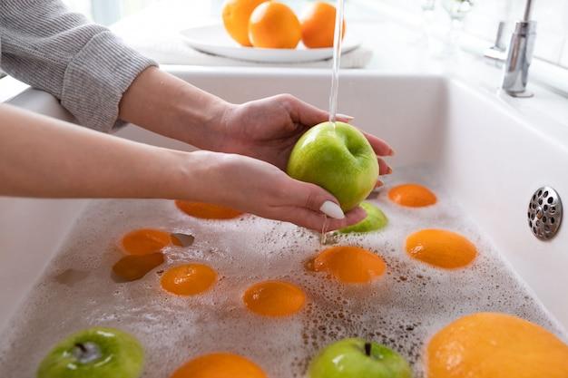 Mulher, lavando, maçã, torneira, em, a, pia, cozinha, embeber, frutas, em, água sabão, completamente, lava