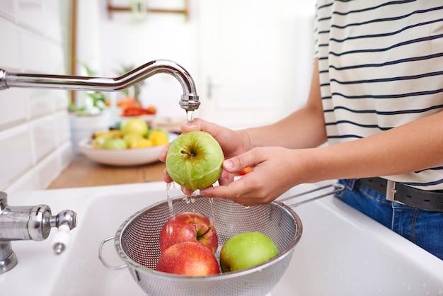 Mulher lavando maçãs frescas da estação