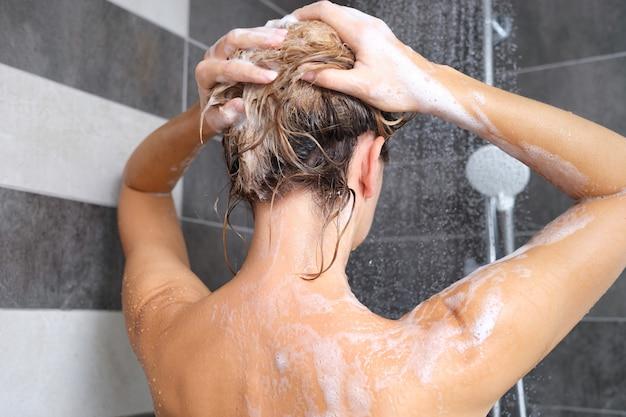 Mulher lavando o cabelo com shampoo na vista traseira do chuveiro