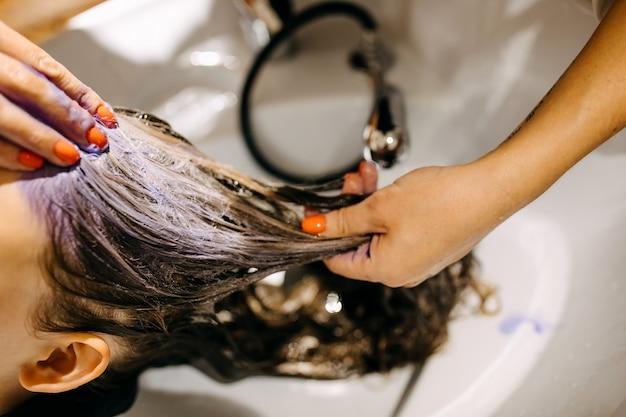 Mulher lavando o cabelo em um salão de beleza, com uma máscara roxa para cabelos loiros