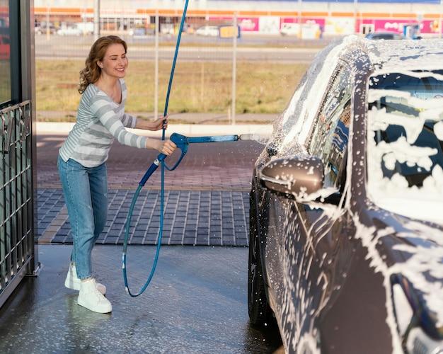 Mulher lavando o carro ao ar livre