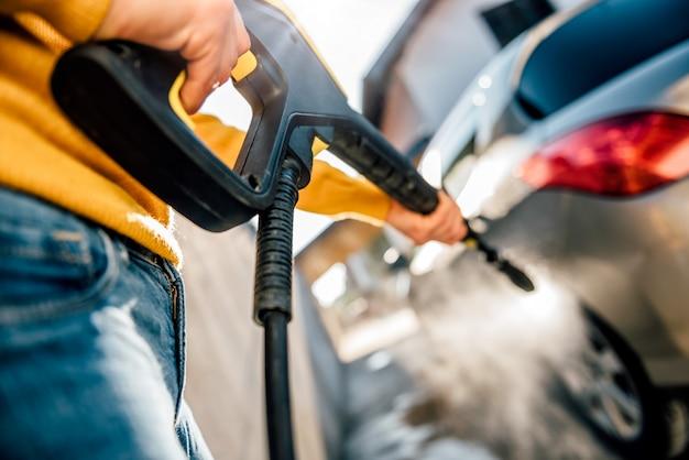 Mulher lavando o carro com lavadora de alta pressão