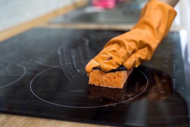 Mulher lavando o painel de cozinha do cooktop moderno na cozinha. limpar