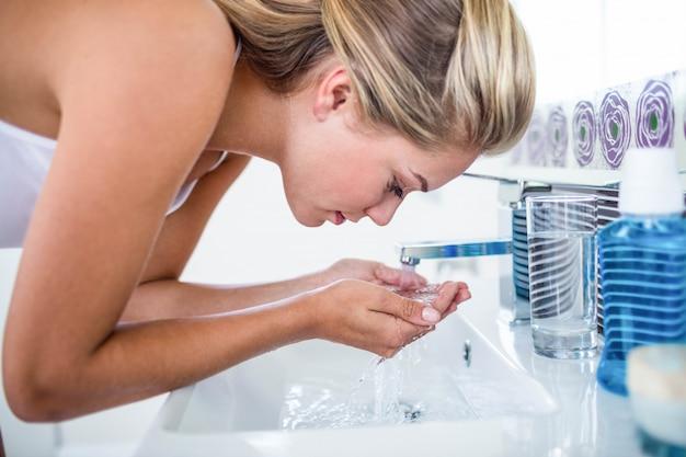 Mulher lavando o rosto no banheiro