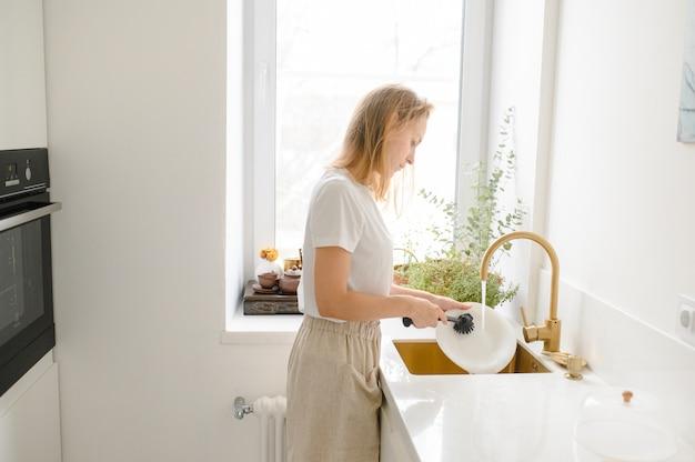 Mulher lavando pratos na cozinha