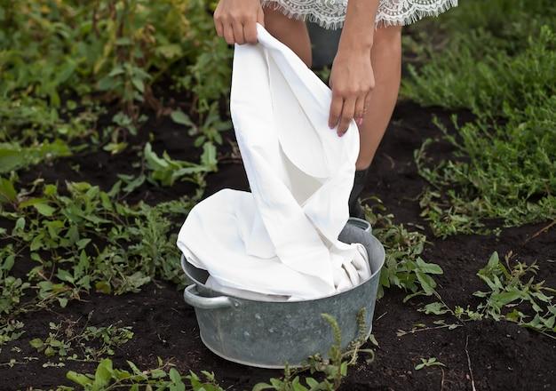 Mulher lavando roupas à mão em uma bacia de lata. estilo retrô. lavagem das mãos.