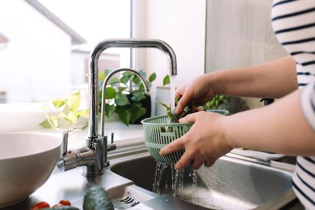Mulher lavando salada verde folhas para salada na cozinha, na pia, sob água corrente.