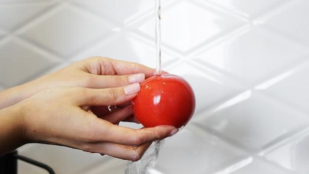 Mulher lavando tomates e tomate nas mãos - fundo branco da cozinha