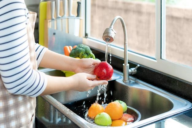 Mulher lavando uma maçã e outras frutas acima da pia da cozinha
