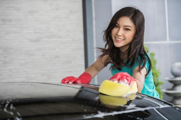 Mulher lavar o telhado do carro com esponja