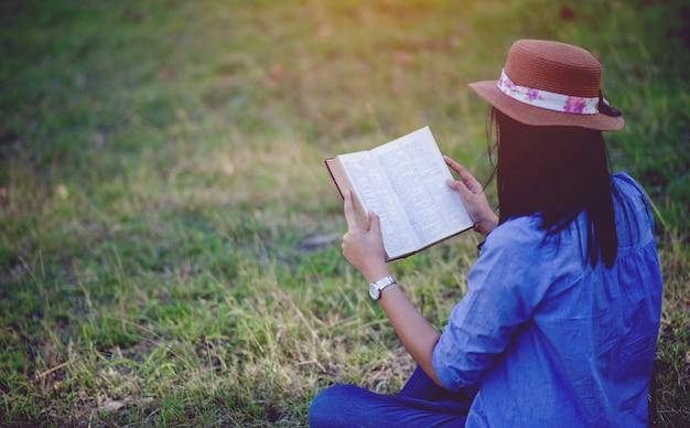 Mulher lê alegremente na floresta que acalma e relaxa os conceitos de leitura e o treinamento do cérebro para ler e lembrar