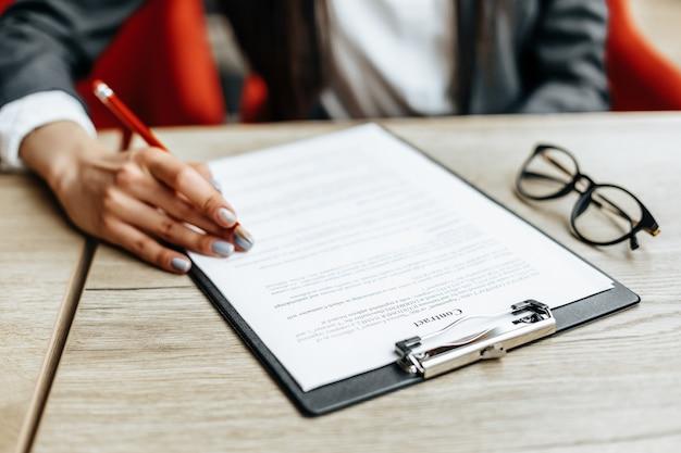Mulher lê e assina documentos