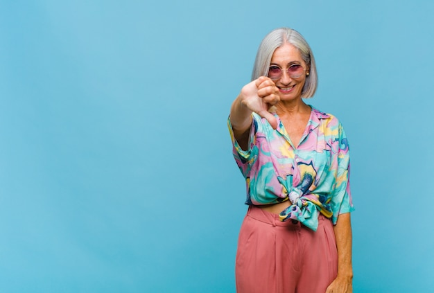Mulher legal de meia-idade se sentindo zangada, irritada, irritada, decepcionada ou descontente, mostrando os polegares para baixo com um olhar sério