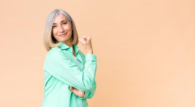 Mulher legal de meia-idade, sentindo-se feliz, satisfeito e poderoso, flexionando o ajuste e os bíceps musculares, parecendo forte após a academia
