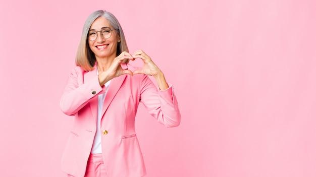 Mulher legal de meia-idade, sorrindo e se sentindo feliz, fofa, romântica e apaixonada, fazendo formato de coração com as duas mãos sobre a parede