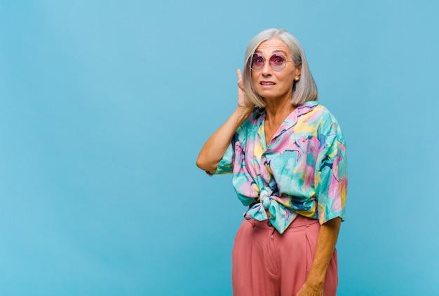 Mulher legal de meia-idade sorrindo, olhando curiosamente para o lado, tentando ouvir uma fofoca ou ouvindo um segredo