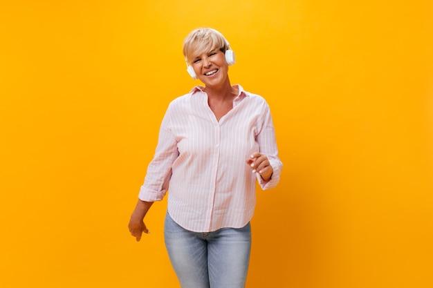 Mulher legal em fones de ouvido sorrindo em fundo laranja