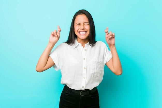 Mulher legal hispânica jovem contra os dedos de um cruzamento de parede azul por ter sorte