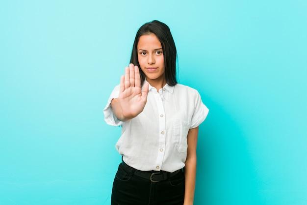 Mulher legal latino-americano nova contra uma parede azul que está com a mão estendida que mostra o sinal de parada, impedindo-o.