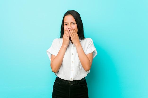 Mulher legal latino-americano nova contra uma parede azul que ri sobre algo, cobrindo a boca com as mãos.