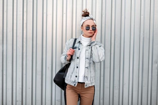 Mulher legal moderna jovem hippie em uma bandana com uma jaqueta jeans de verão em um suéter vintage branco de malha em calças bege com uma bolsa preta em óculos de sol perto da parede de metal cinza. garota de férias.