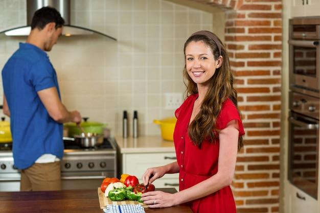 Mulher, legumes chopping, e, cozinhar homem, ligado, fogão, em, cozinha, casa