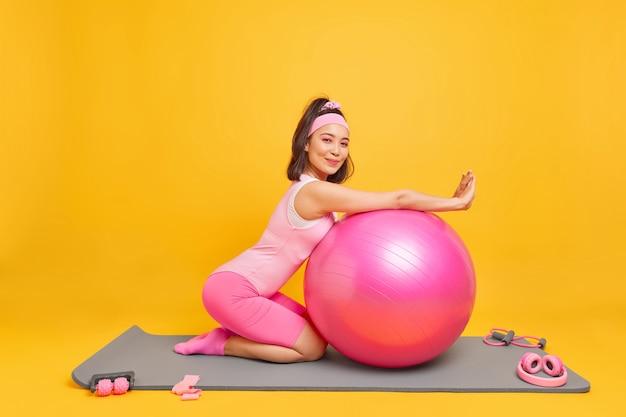 Mulher lenas na bola de fitness tem expressão satisfeita vestida com roupas esportivas faz uma pausa após o treino em casa gosta de poses de ginástica e aeróbica no tapete interno