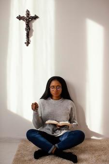 Mulher lendo a bíblia dentro de casa
