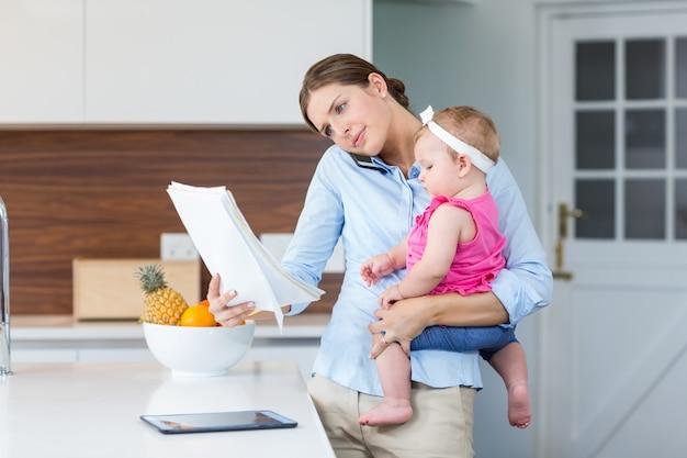Mulher lendo documentos enquanto carregava bebê