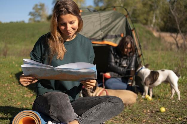 Mulher lendo e cachorrinho brincando com a amiga