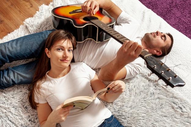 Mulher lendo e homem tocando violão