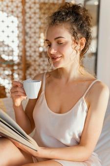 Mulher lendo e tomando café