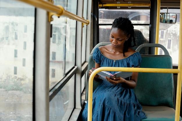 Mulher lendo em um ônibus médio