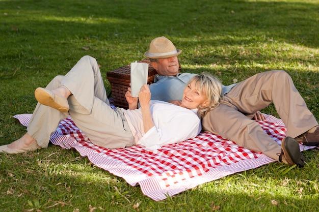 Mulher lendo enquanto o marido está dormindo no parque