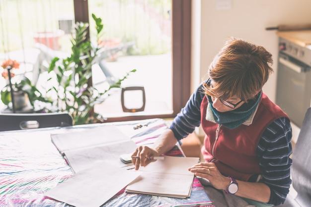 Mulher lendo jornais na mesa. casa interior em contraluz. imagem enfraquecida.