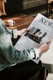 Mulher lendo jornal em um café