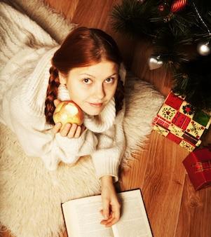Mulher lendo livro de natal na frente da árvore