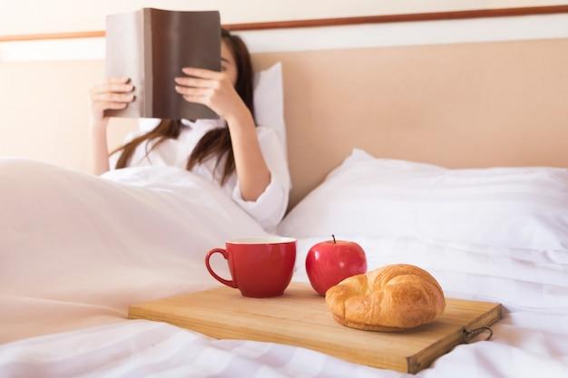 Mulher lendo livro e bebendo café na cama durante a manhã