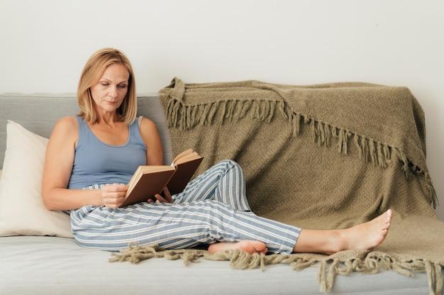 Mulher lendo livro em casa durante a quarentena