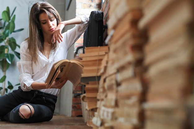 Mulher lendo livros no chão