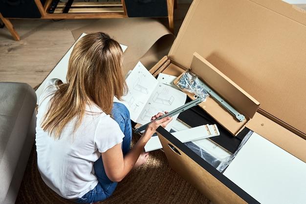 Mulher lendo manual de instruções para montar móveis