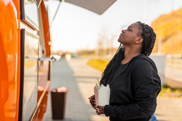 Mulher lendo menu no caminhão de comida segurando uma caixa de comida