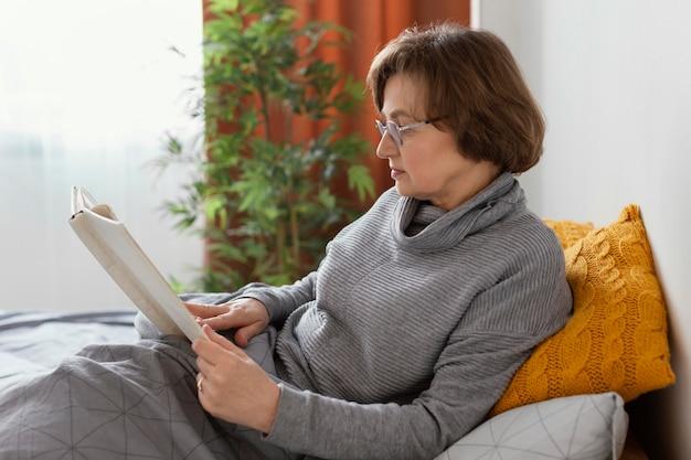 Mulher lendo na cama tiro médio