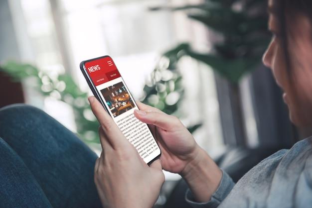 Mulher lendo notícias ou artigos em um aplicativo de tela de celular em casa.