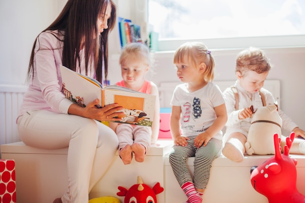 Mulher lendo para crianças na escola