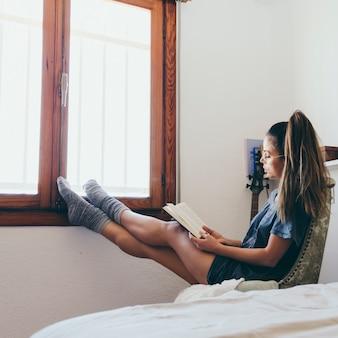 Mulher lendo perto da janela