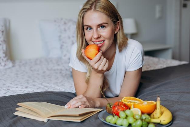 Mulher lendo um livro deitada na cama, comendo frutas e olhando para a câmera.
