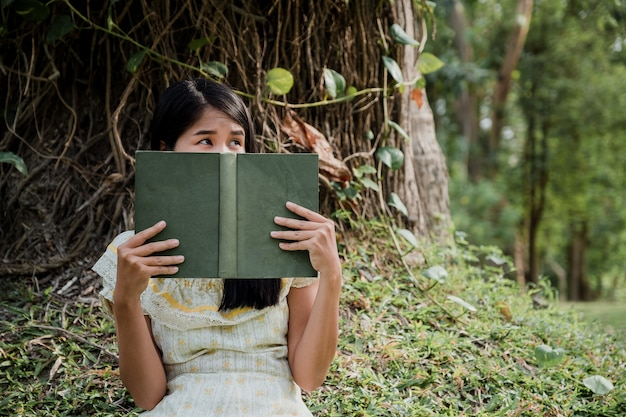 Mulher lendo um livro e cobrindo o rosto no parque.